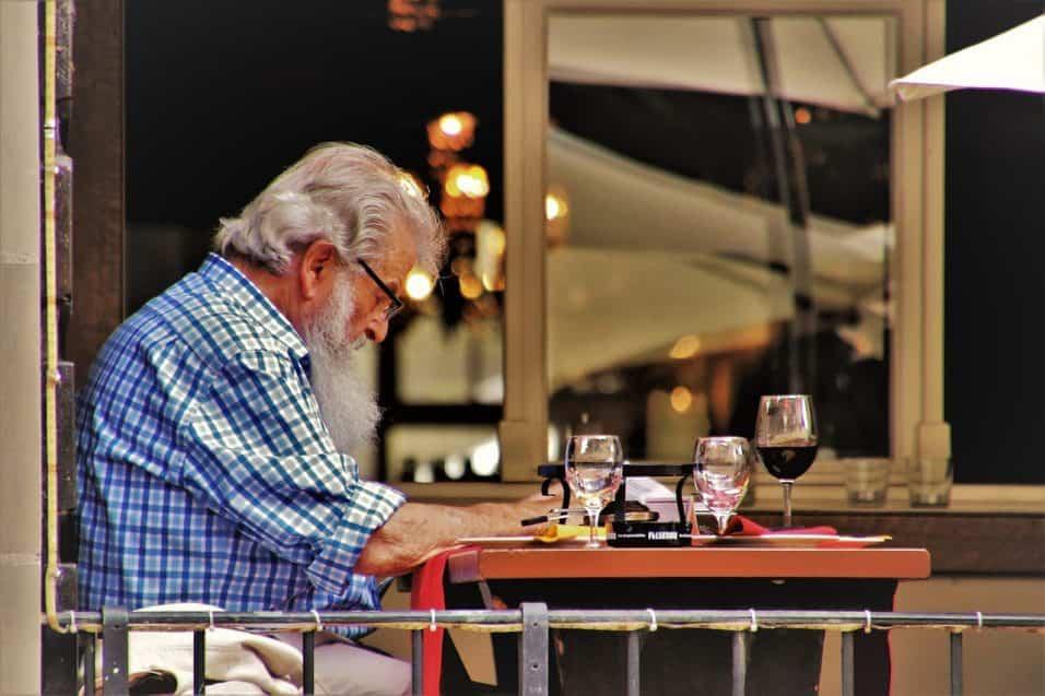 Uomo anziano che beve vino